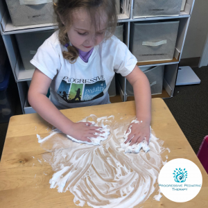 Sierra practices letter formation by drawing in shaving cream.