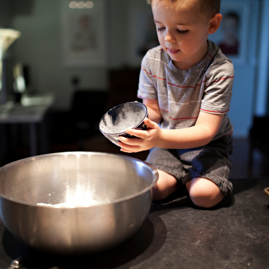 child pouring dry ingredients into a bowl.