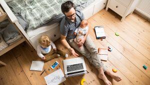 Un padre está trabajando desde casa con sus hijos.