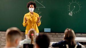 Una maestra lleva una máscara mientras enseña a sus alumnos.