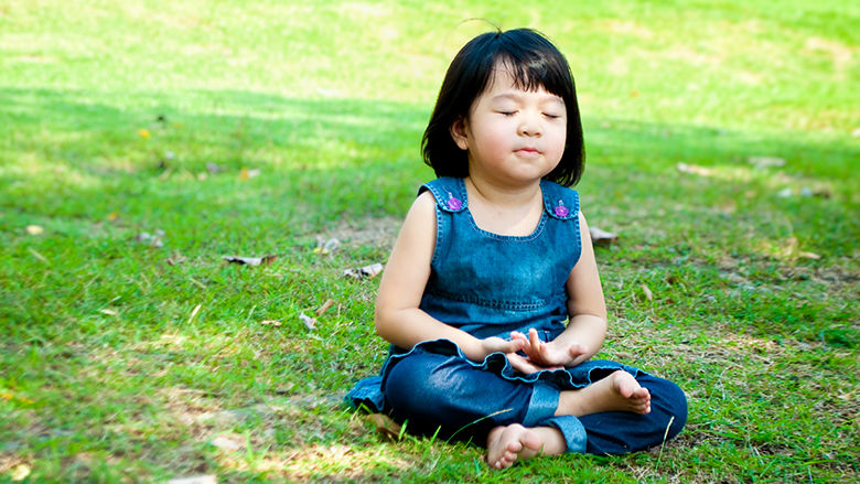 Child with eyes closed breathing in through the nose while sitting on the grass