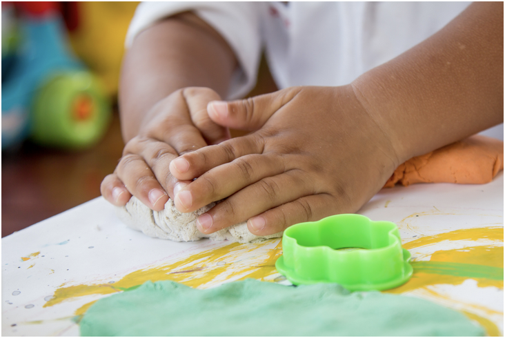 Child's hands molding play doh