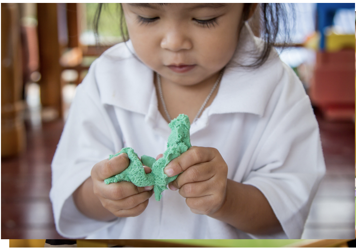 Child playing with green playdoh using both hands at midline