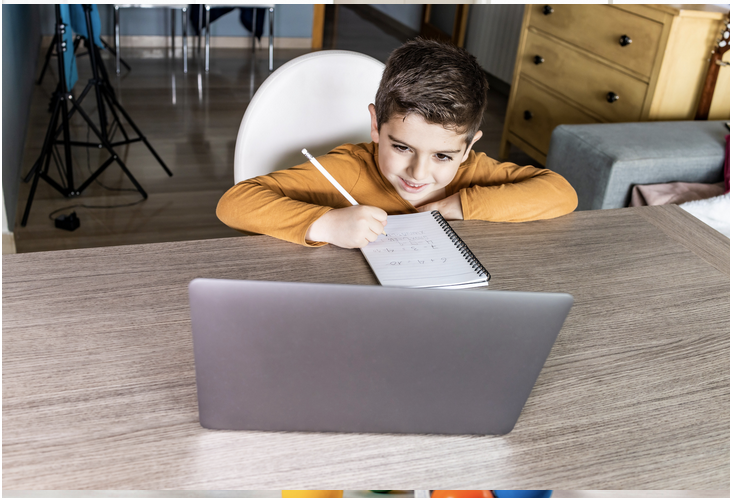 Child leaning forward on to desk, writing on paper and looking at a computer screen