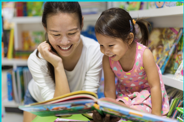 Mother and daughter reading a book aloud