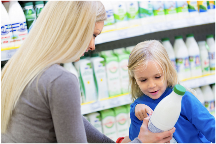Child pointing to a bottle that her mother is holding