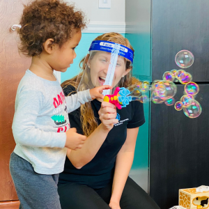Child and therapist playing with bubbles